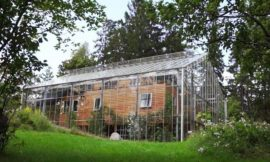 Family wraps home in greenhouse to warm it naturally
