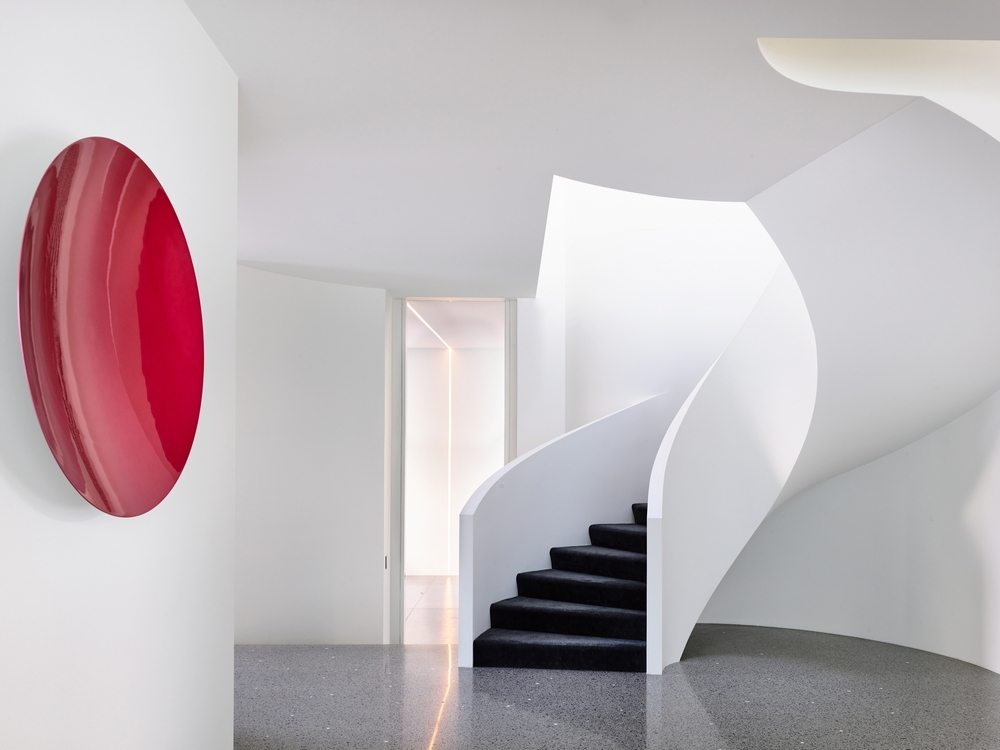 A sculptural staircase that almost looks like art leads to the upper floor..
