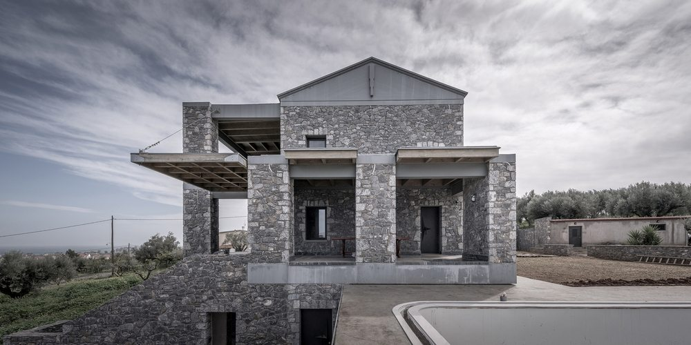 Earth-colored stones allow the house to blend well with the surrounding olive trees.