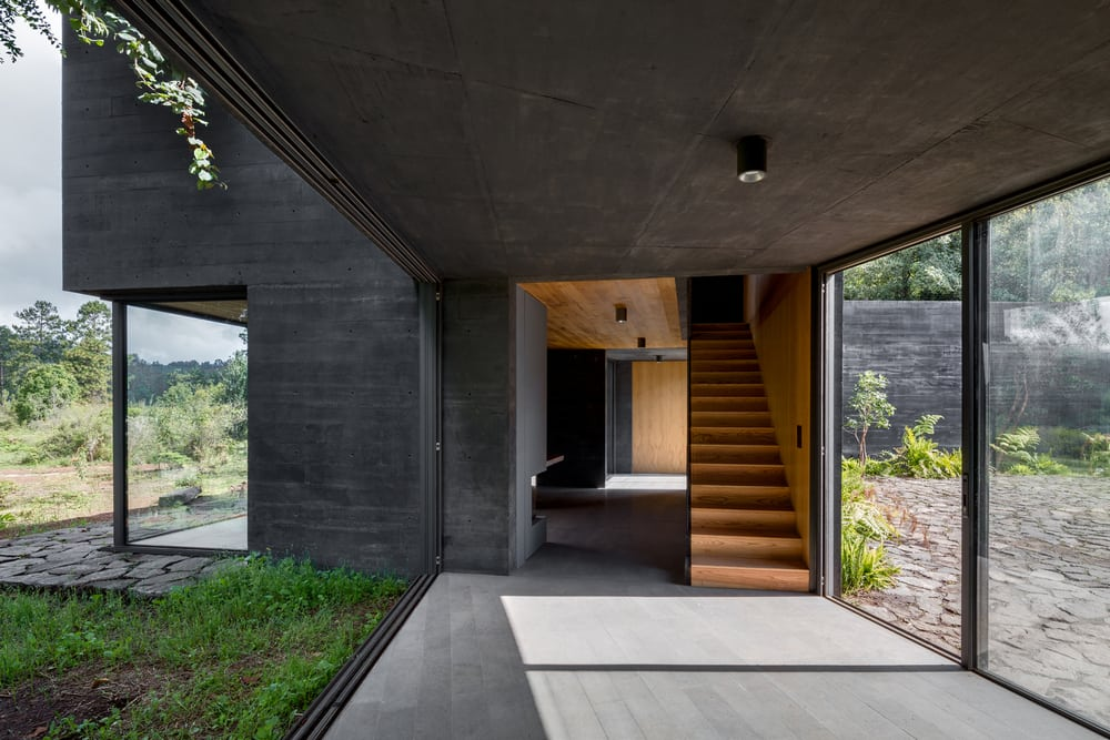 A neutral-palette interior contrasts well with the dark, black concrete of the facade.