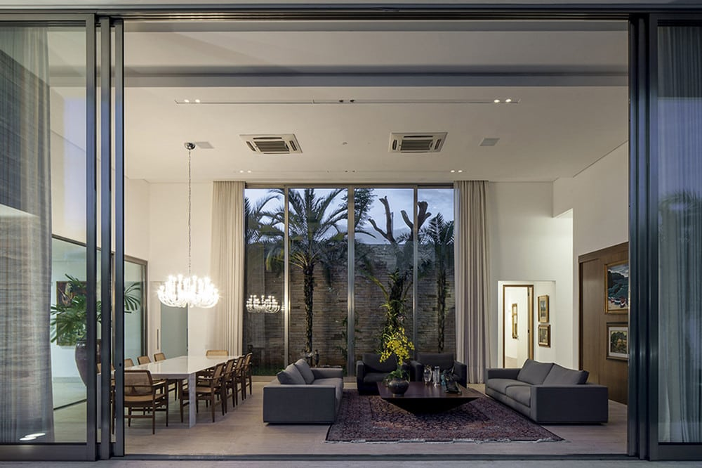 TB House features glass walls with bright and contemporary interiors .