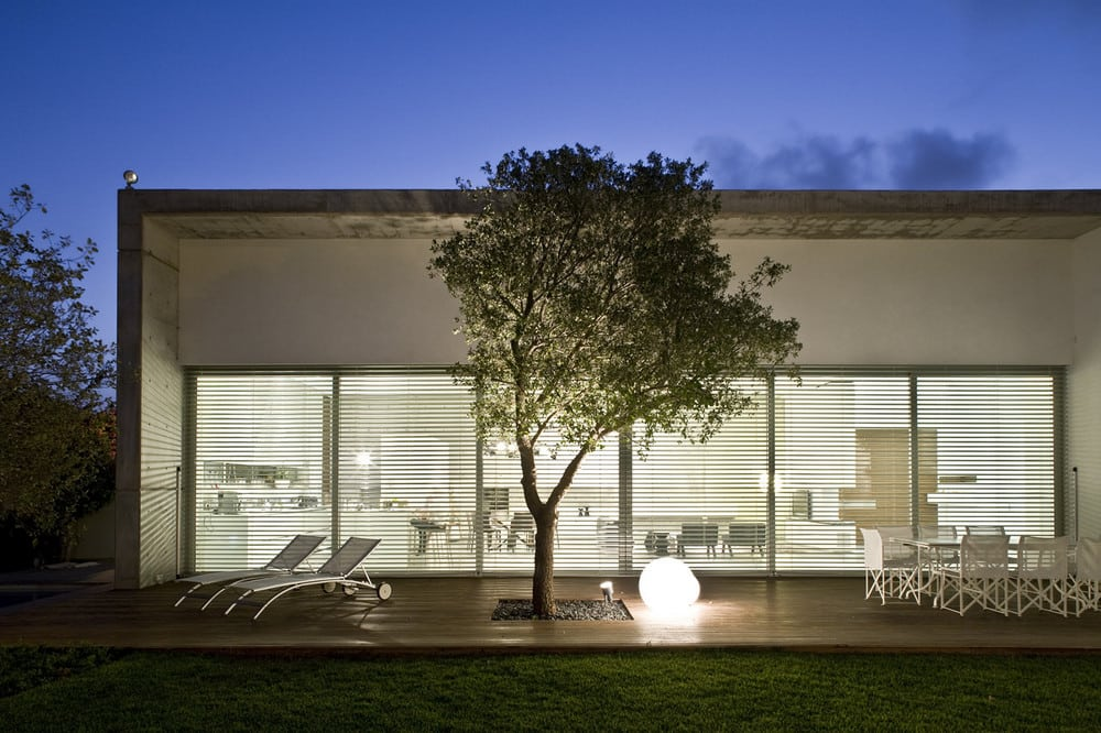 The hard, heavy concrete is balanced by large glass windows that allow plenty of sunlight into the home.